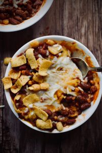 a bowl of vegetarian wheat berry chili. cheese is melted on top of the chili and there are corn chips sprinkled about.