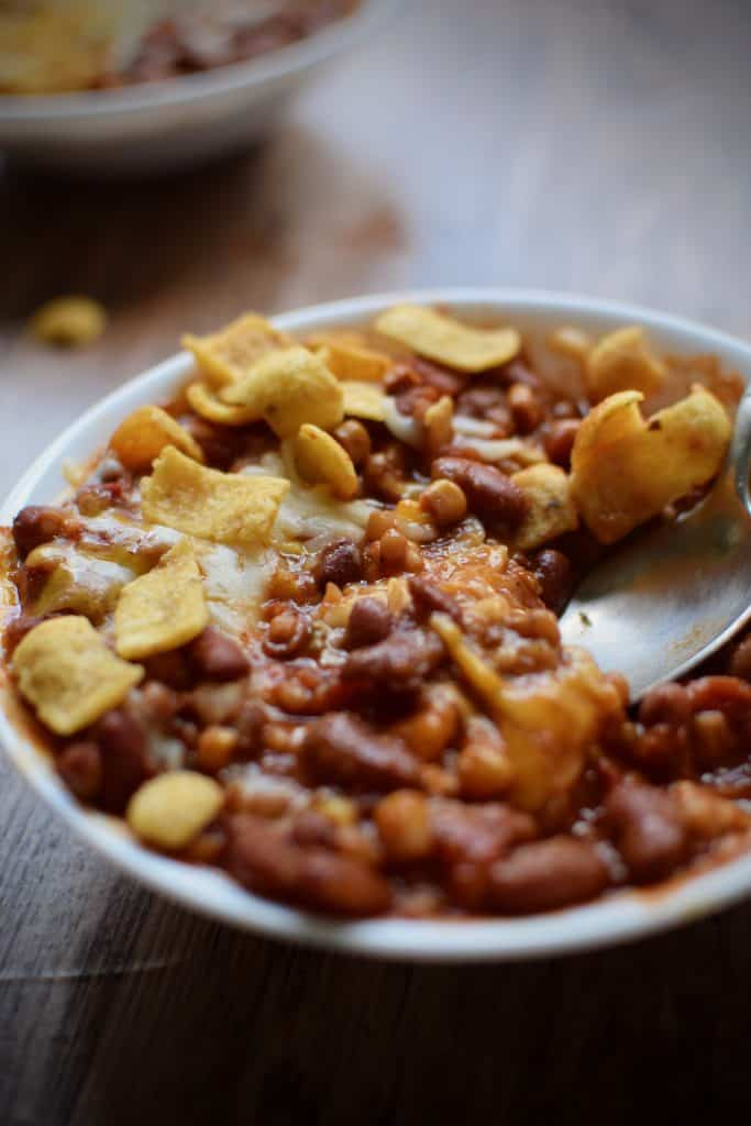 close up of healthy and easy instant pot vegetarian chili with wheat berries.  On top of the chili is melting cheese and corn chips.  A spoon is scooping some chili out.