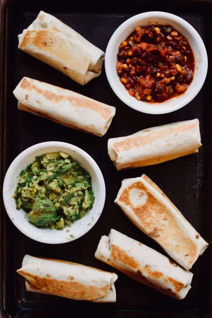 healthy, freezer bean and cheese burritos arranged with guacamole and salsa. theincrediblebulks.com