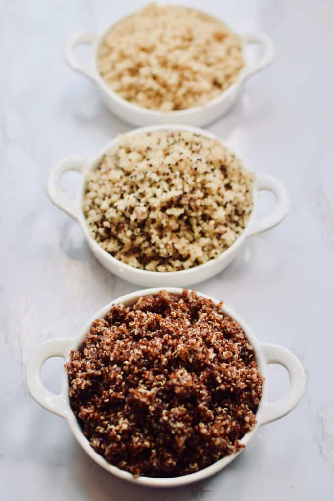 red quinoa, mixed quinoa, white quinoa in three separate bowls. theincrediblebulks.com