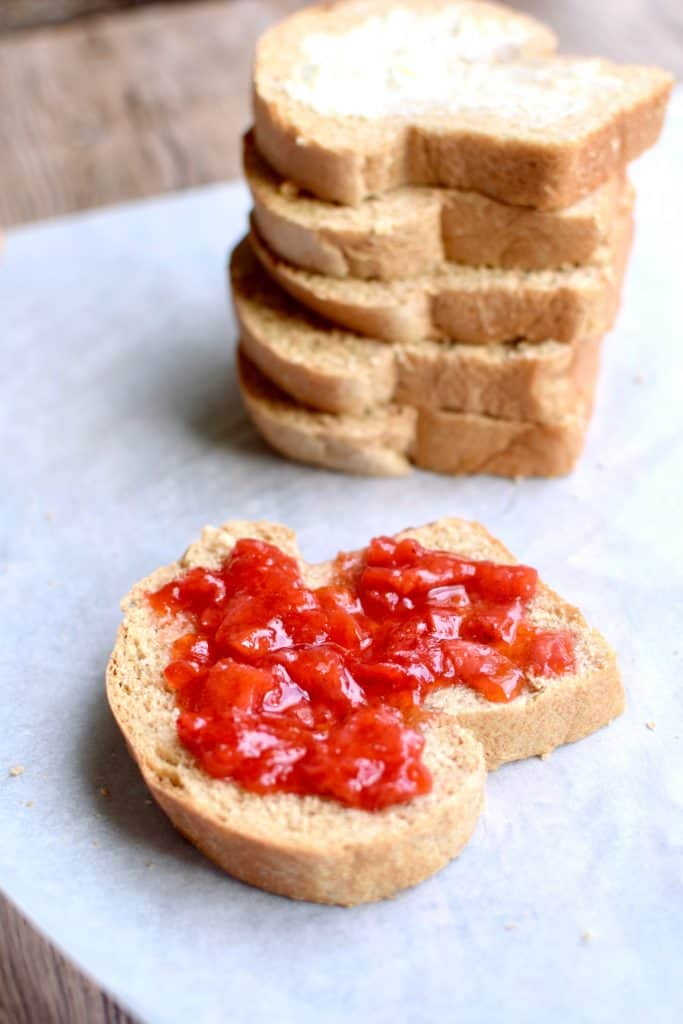 A slice of whole wheat bread covered in Strawberry jam.  In the background is a stack of sliced bread.  TheIncredibleBulks.com