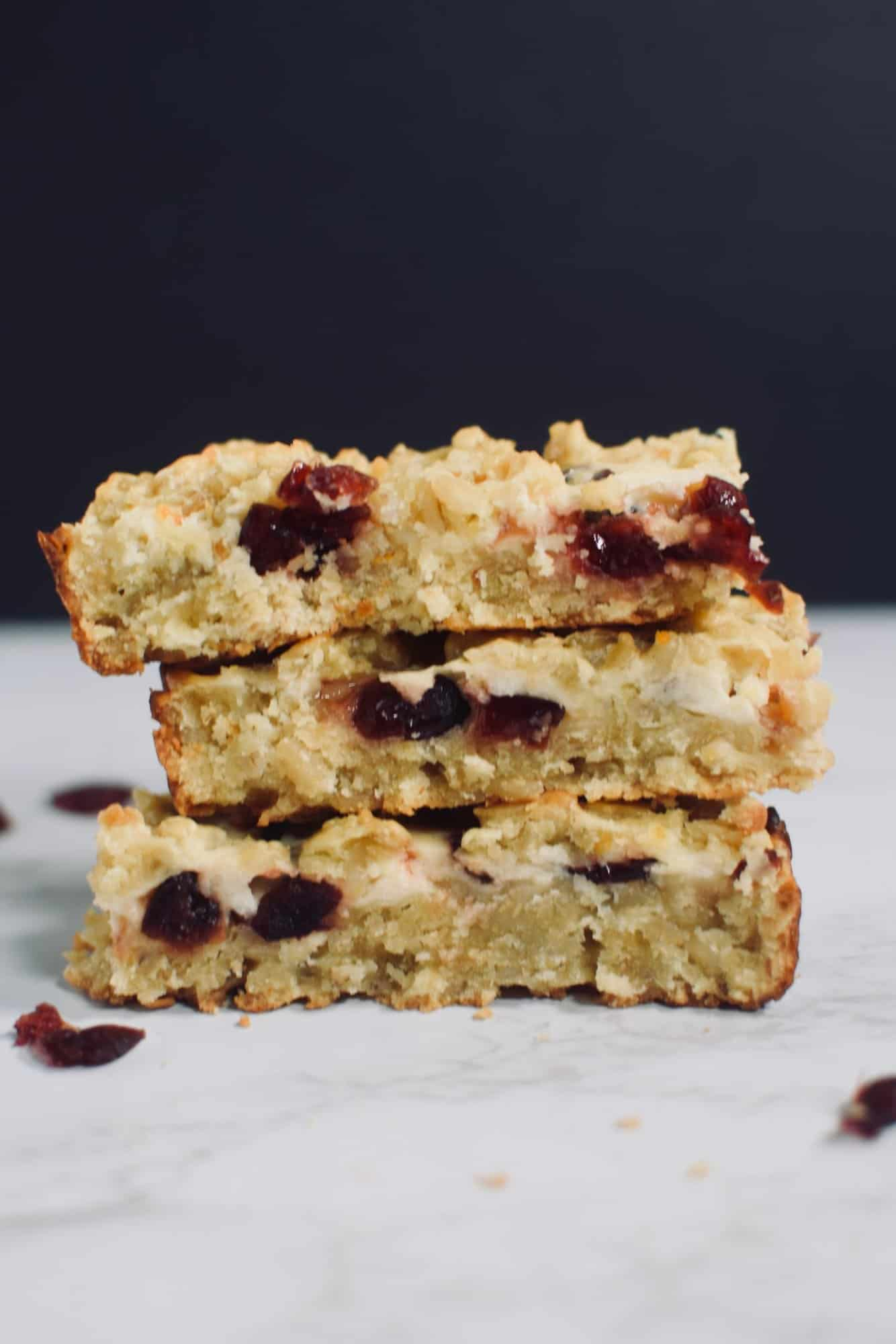 3 Cranberry Orange Barley Bars stacked on top of one another. From TheIncredibleBulks.com