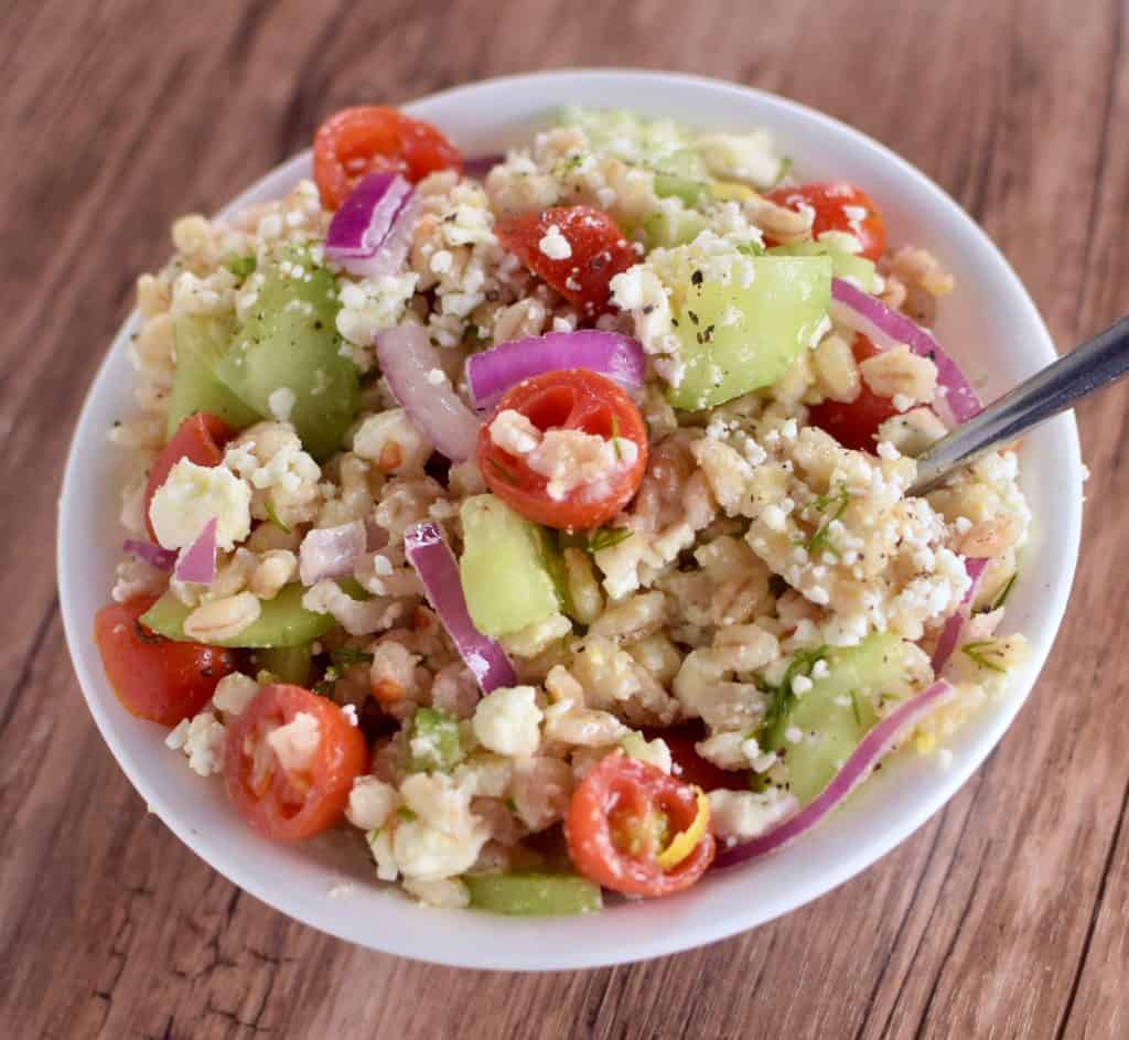 A Bowl of Mediterranean Barley Salad featuring grape tomatoes, purple onions, cucumbers, and feta with a Lemon Dill Dressing. The