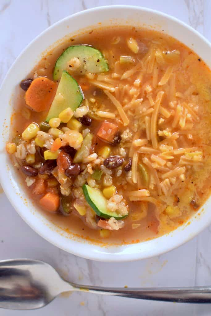 A bowl of Mexican bean and barley soup featuring corn, zucchini, carrots, black beans and barley in a tomato based broth.  Cheddar Cheese is melting into the soup on top and a spoon is below the bowl, ready for eating. theincrediblebulks.com