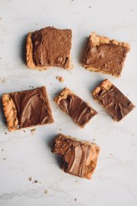 6 chocolate peanut butter oatmeal bars arranged on a white background. One has had a bite taken out of it. Brought to you by TheIncredibleBulks.com