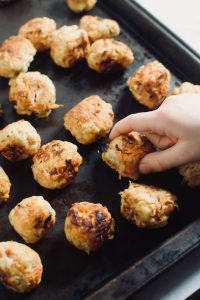 A child's hand is taking a chicken meatball from a pan that is full of meatballs. theincrediblebulks.com