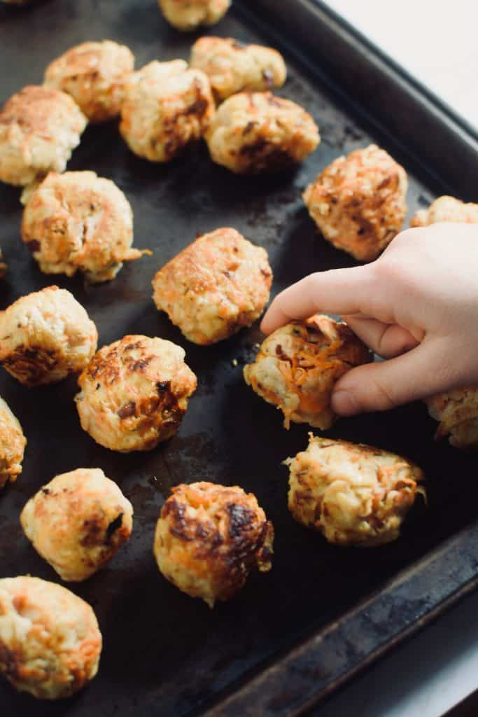 A child's hand is taking a fried chicken meatball from a pan that is full of meatballs. theincrediblebulks.com
