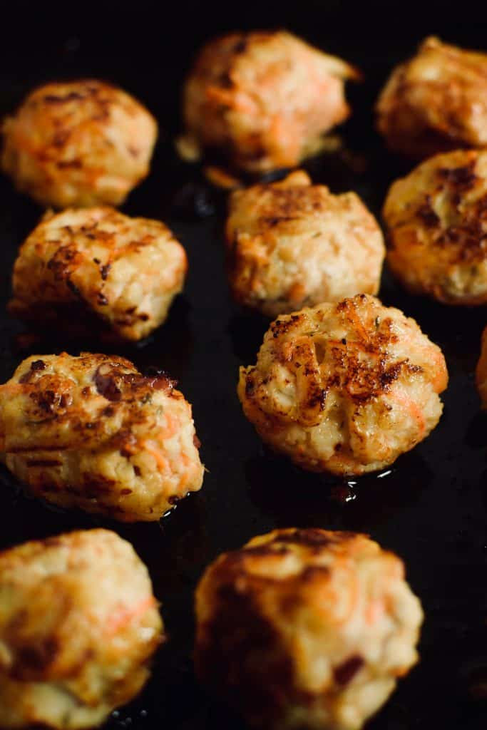A close up of several fried chicken meat balls with carrots and apples.  Theincrediblebulks.com