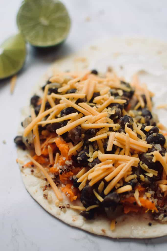 the contents of an ungrilled quesallas are shown cut in a close up shot. You can see quinoa, black beans, sweet potatoes and cheddar cheese. A lime is in the background.  theincrediblebulks.com