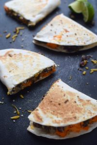 4 sweet potato black bean quesadillas featuring quinoa. They are cut into 4 triangles and arranged with a lime.