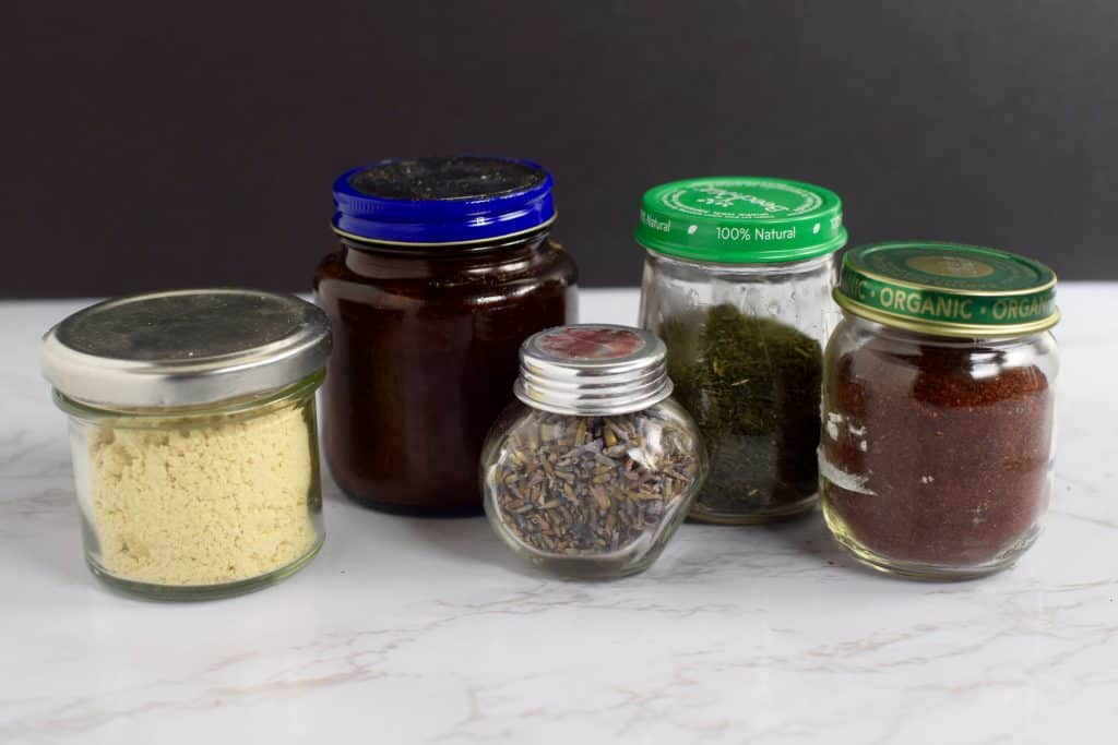 5 jars of varying sizes are shown with different spices in them.  The jars are recycled baby food jars.  theincrediblebulks.com