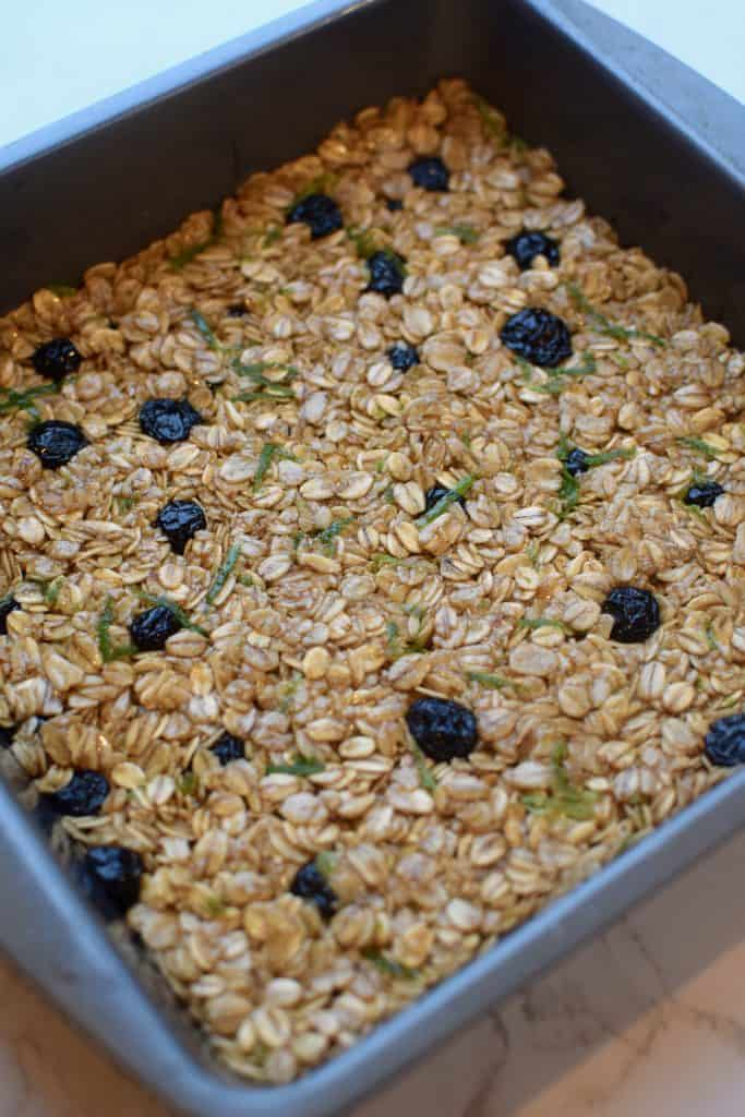 A 8-inch square pan in shown full of soft and chewy granola bars.  Dried blueberries and lime zest can be seen in the granola bars.  TheIncredibleBulks.com