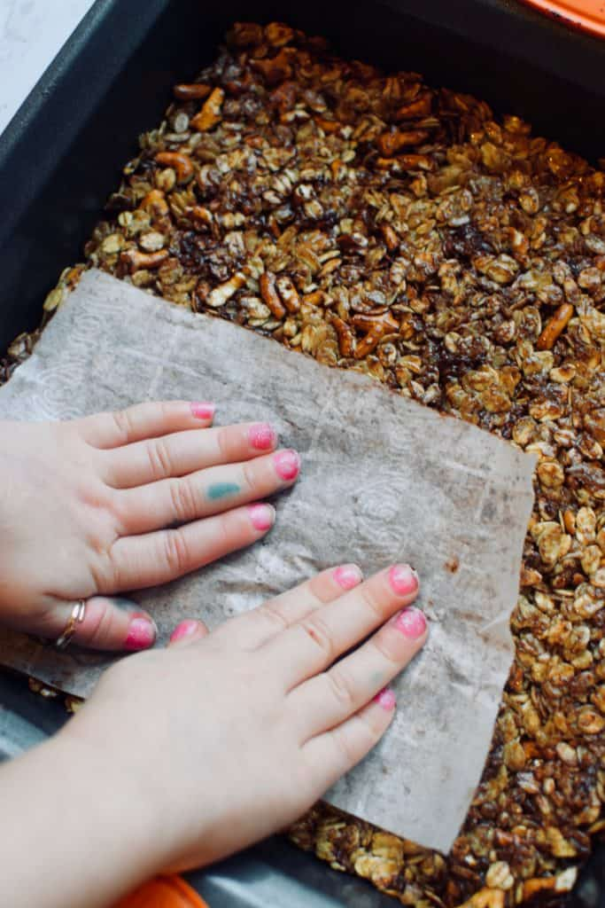 A child's hands are seen using parchment paper to press homemade granola bars into a 9 inch square pan.  Broken bits of pretzels and melted chocolate can be seen in the granola bars.  TheIncredibleBulks.com