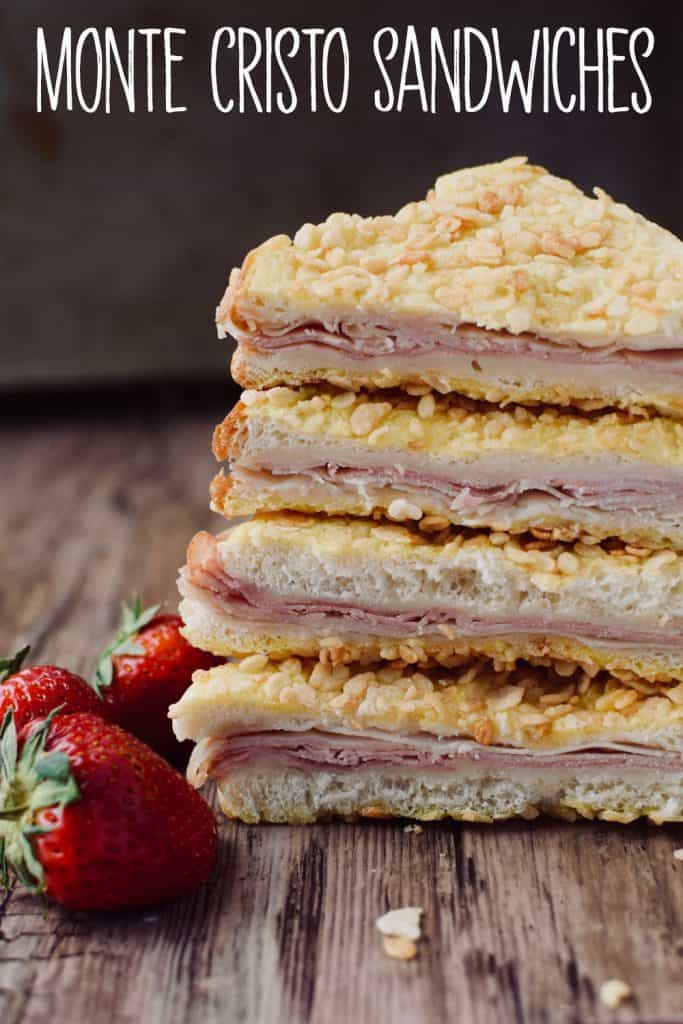 "A stack of 4 Monte Cristo sandwich triangles.  The meat and cheese can be seen between bread slices.  There are strawberries next to the sandwiches.  The words ""Monte Cristo Sandwiches"" are written above."