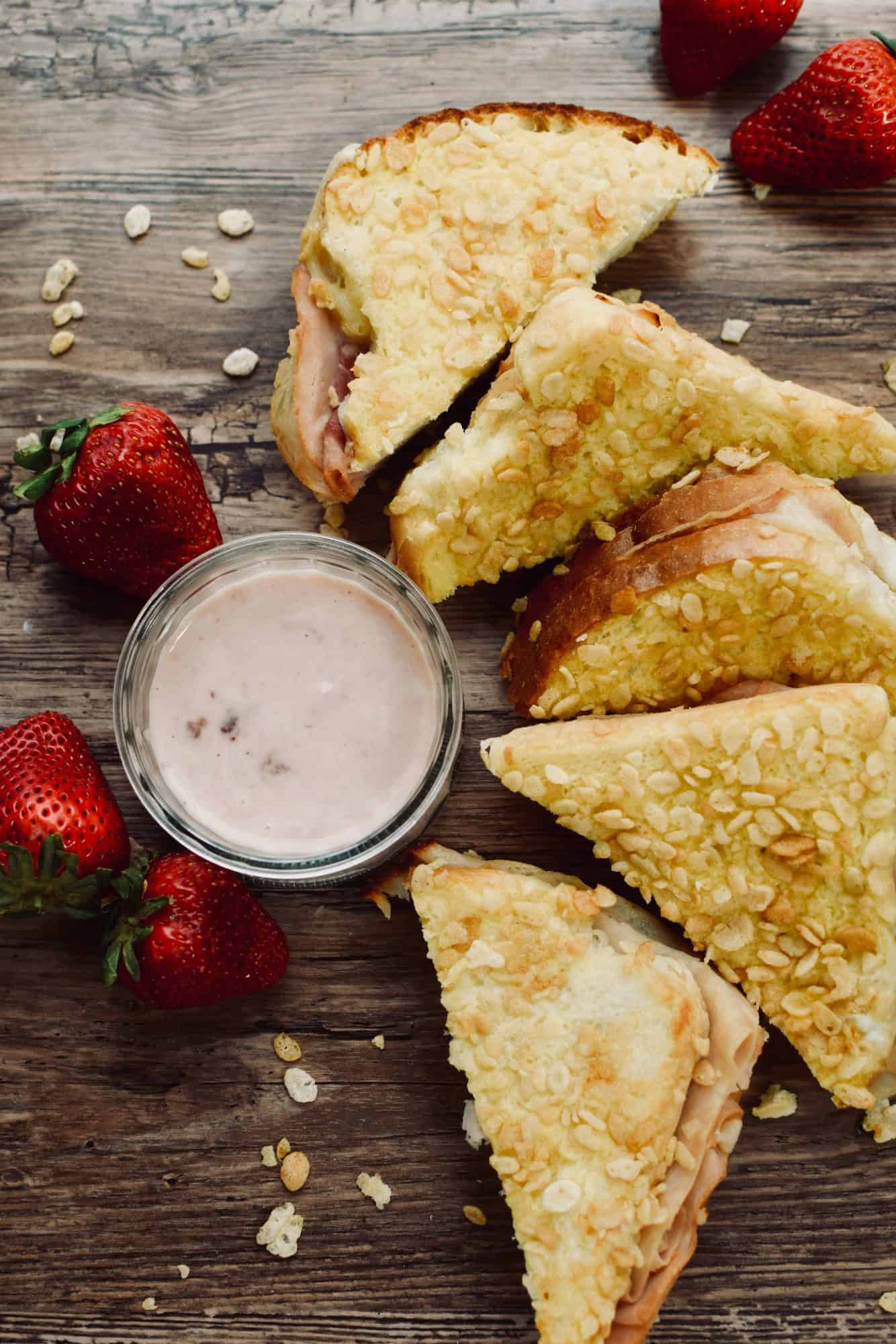 5 triangles of Monte cristo sandwiches are arranged on a table next to a small bowl of strawberry dipping sauce. Strawberries are next to the sandwiches.