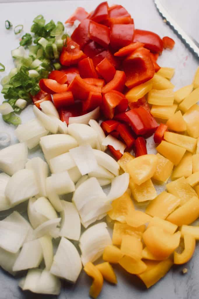 green onions, red peppers, yellow peppers and onions are all diced into pieces and resting on a cutting board.