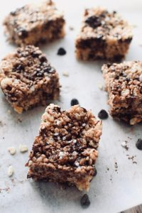 5 squares of salted chocolate rice krispie treats on a piece of parchment paper. chocolate chips and pieces of cereal are also scattered about.
