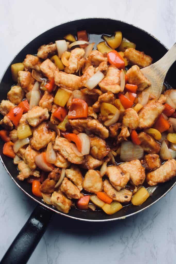 a black frying pan is full of sweet and sour chicken.  With the chicken, bell peppers and onions can be seen.  A wooden spoon is stirring it.
