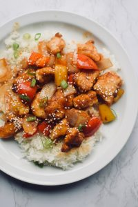 white rice and sweet and sour chicken on a plate. It is garnished with green onions and sesame seed.