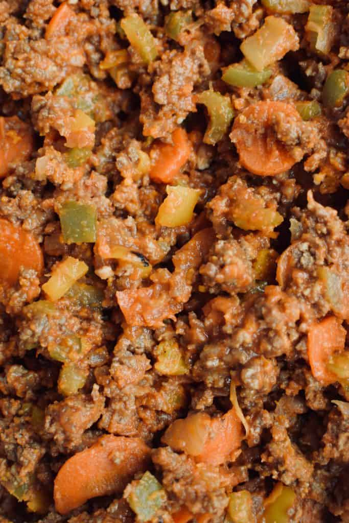 a close up of healthier sloppy joe filling. meat, as well as carrots, onions, peppers and celery slices can be seen.