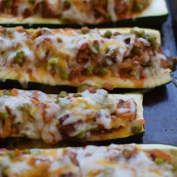 5 zucchini boats on a cookie sheet. The boats are stuffed with sausage, mushrooms, and peas. cheese is melted on top.