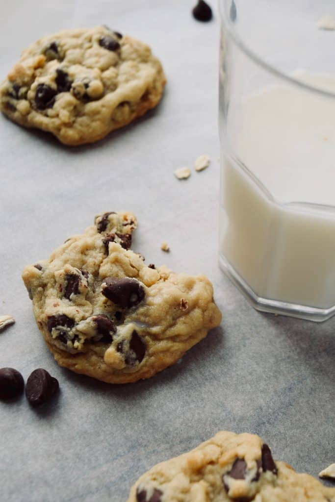 3 cookies and a cup of milk.  A few chocolate chips and oatmeal has spilled on the countertop.