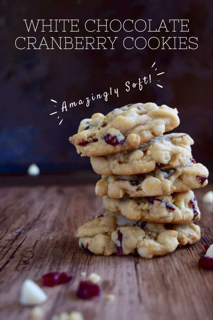 "a stack of 5 cookies on a wooden table with a black background. A few white chocolate chips and craisins are spread around.  The words ""White Chocolate Cranberry Cookies"" and ""amazingly soft"" are written over the photo."
