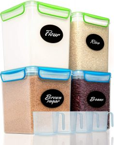 4 large square storage containers holding flour, rice, brown sugar and beans.  4 measuring scoops are in front.