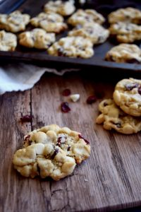 A cookie on a wooden table, in the background, more cookies are on a baking sheet.