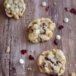 3 white chocolate cranberry cookie on a wooden table and some crumbs and extra chocolate chips surround the cookie.