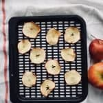 10 apple chips on an air fryer tray. A towel is underneath and 2 apples are next to it.
