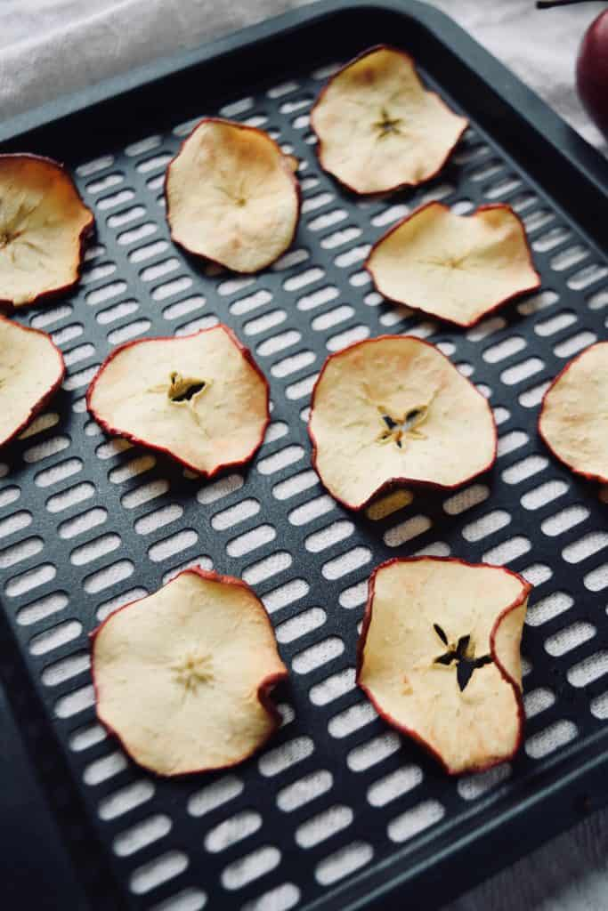 10 apple chips on an air fryer tray. A towel is underneath .