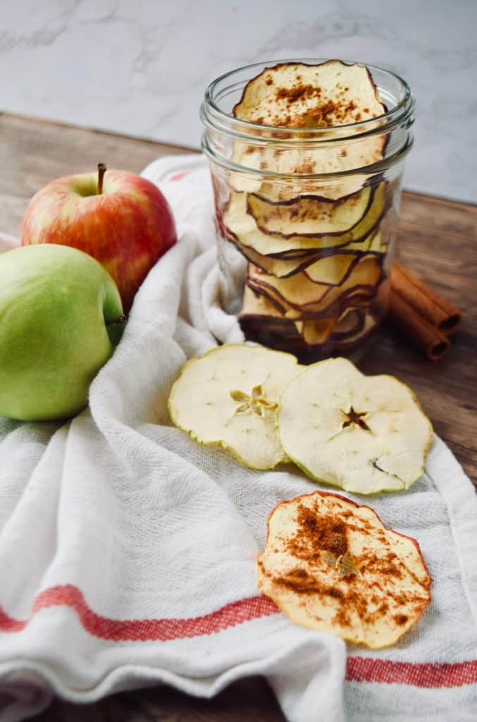 A mason jar full of dehydrated apple chip. 2 apples are next to it, and a few chips lay next to the jar on a towel.