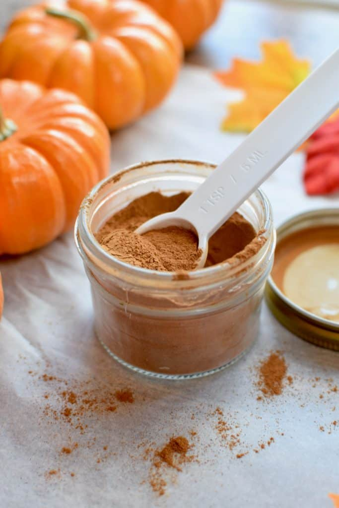 a small jar of pumpkin pie spice. A tsp is scooping some out. 3 Pumpkins are next to it and a few fall leaves.