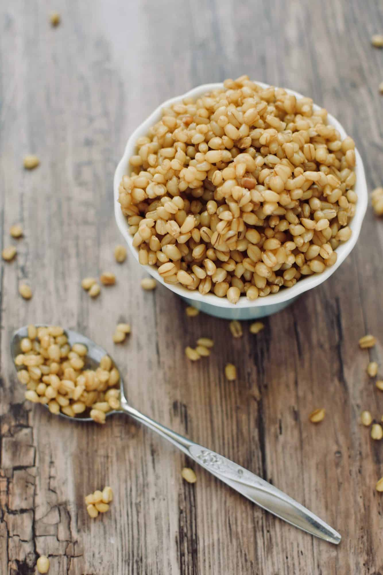 a small bowl of wheat berries on a wooden table. A spoon full of grains is next to the bowl.