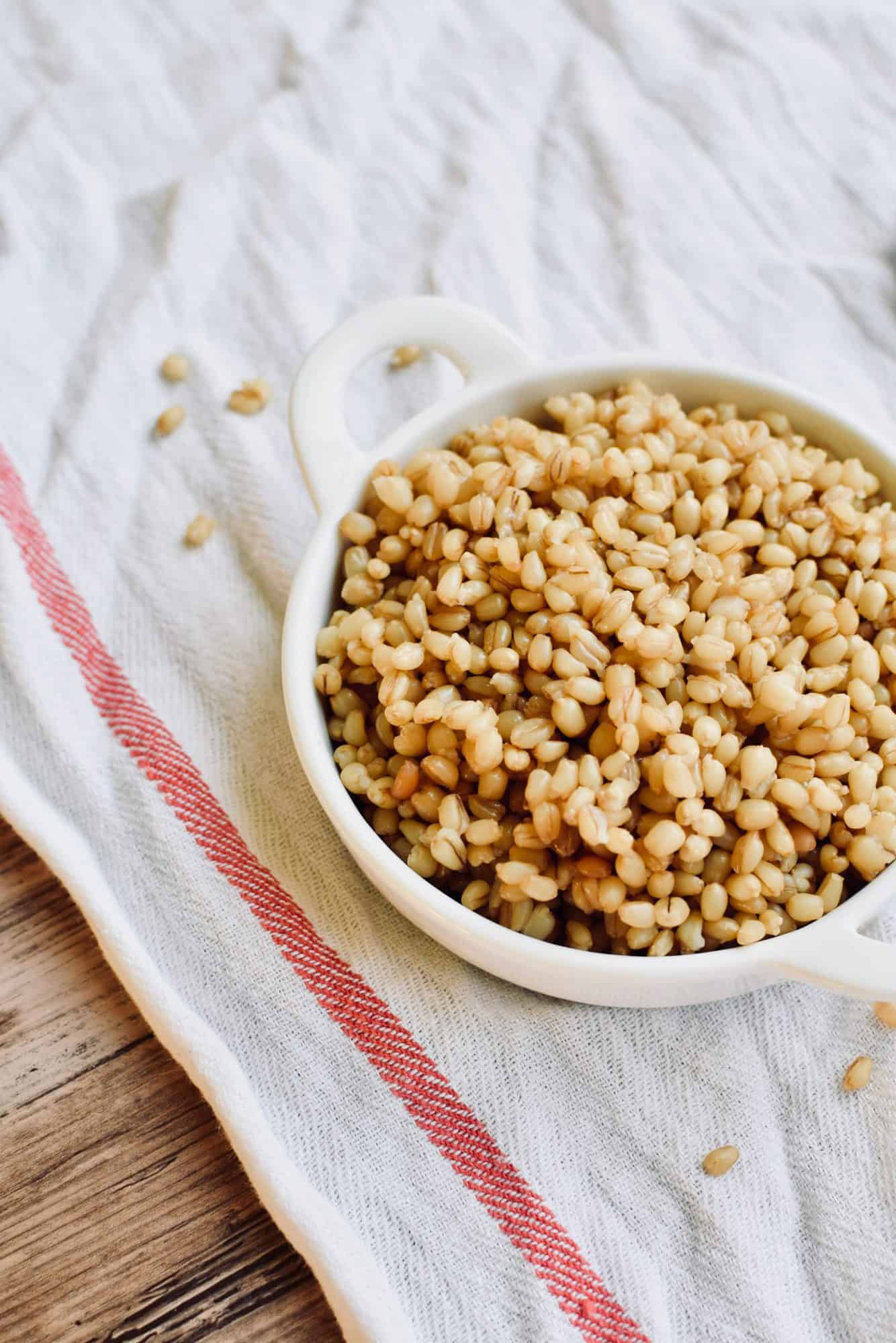 A small bowl of wheat berries on a white tea towel. A few grains have fallen out.