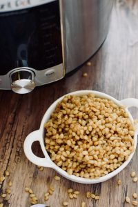 A small bowl of wheat berries next to an Instant Pot.