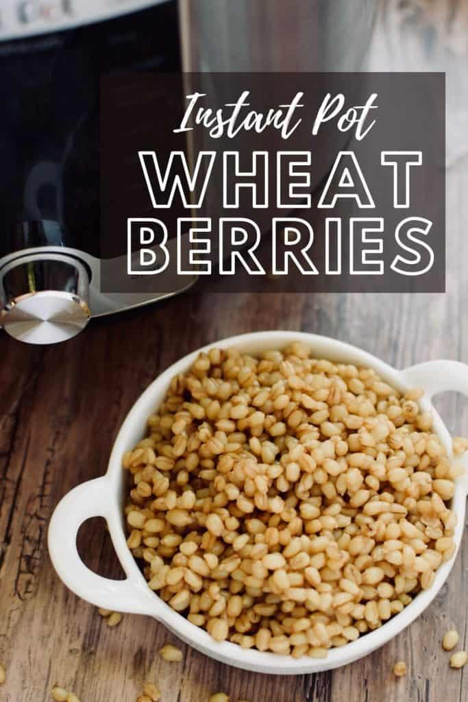 """A small bowl of wheat berries next to an Instant Pot. The words, """"Instant Pot Wheat Berries"""" are written across the top."""